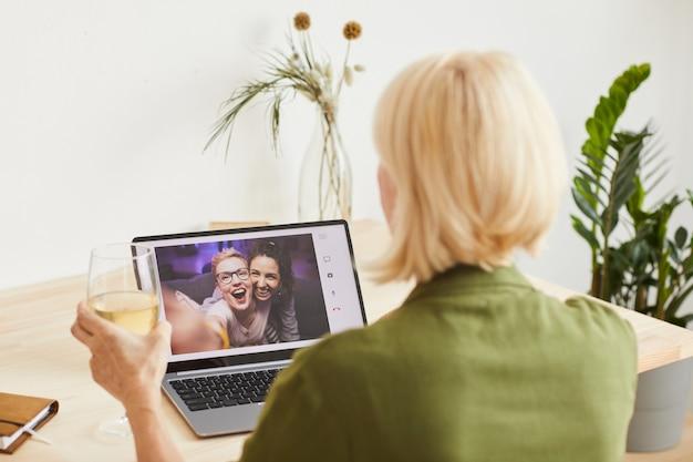 Vista posteriore della donna con i capelli corti biondi che tiene un bicchiere di vino e celebra la vacanza con i suoi amici online sul computer portatile