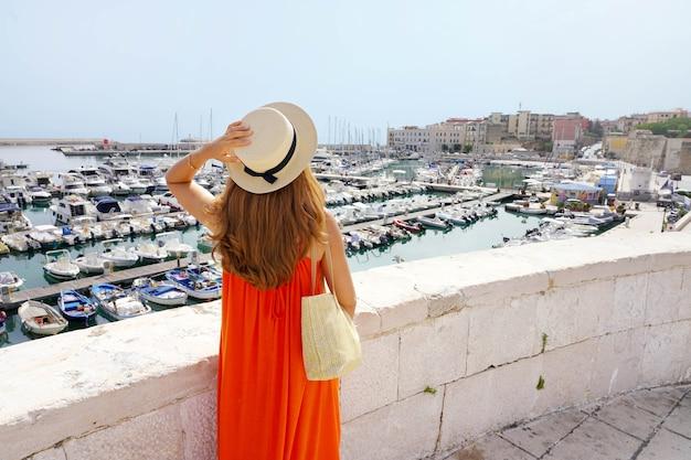 Vista posteriore della donna con abito arancione cercando porto di bisceglie dalla città vecchia, puglia, italy