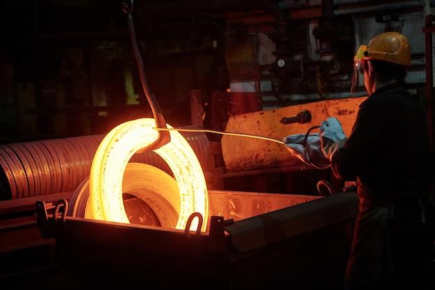 Vista posteriore del lavoratore con casco che lavora con il metallo in una fabbrica di metallo