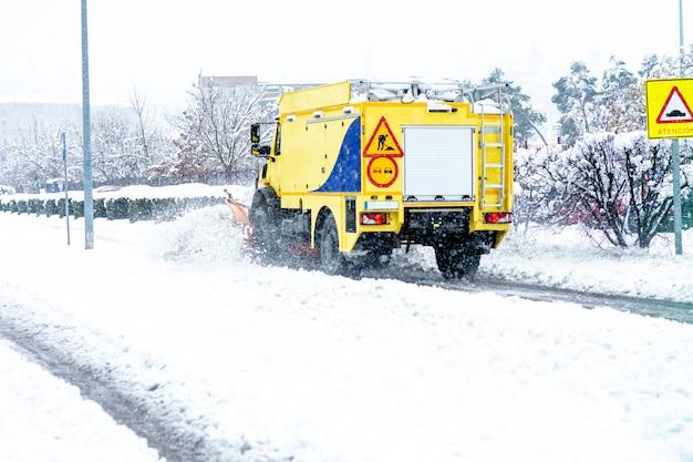 Vista posteriore di uno spazzaneve giallo che pulisce la neve su un viale principale della città.