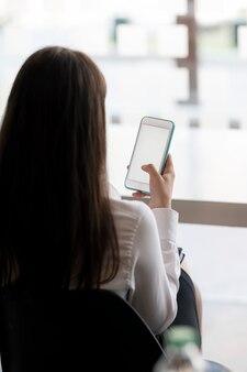 Vista posteriore di una giovane donna asiatica che tiene in mano uno smartphone con schermo vuoto mentre è seduto nella stanza dell'ufficio, vista verticale.
