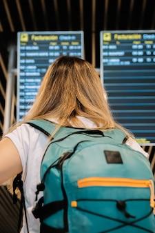 Vista posteriore di una giovane donna bionda che guarda gli schermi delle informazioni sui voli dell'aeroporto.