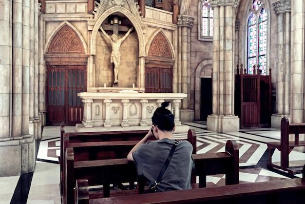 Retrovisione di giovane uomo casuale che prega in una chiesa.
