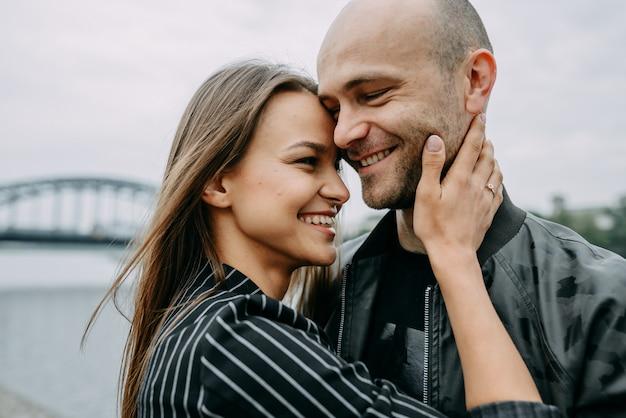 Retrovisione di una giovane coppia che si siede dal lato di un lago che tocca le loro teste nell'amore.