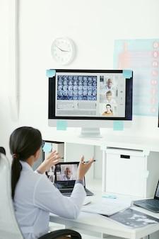 Vista posteriore del giovane medico a parlare con i suoi colleghi sul monitor del computer durante la conferenza online in ospedale