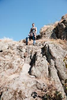 Vista posteriore di un uomo giovane escursionista con zaino all'aperto su una scogliera