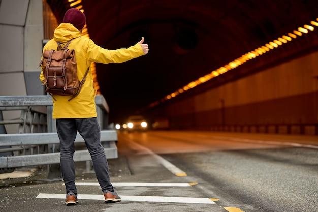 Vista posteriore del giovane che fa l'autostop in giro per il paese, cercando di catturare un'auto di passaggio per viaggiare. l'uomo hipster caucasico in cappotto giallo con zaino è andato in autostop a sud.