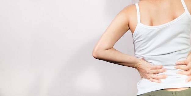 Retrovisione di un giovane che tiene la sua schiena nel dolore, isolato su fondo bianco.