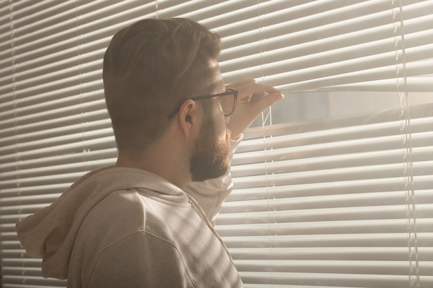 La vista posteriore del giovane con la barba fa capolino attraverso il foro nelle persiane della finestra e guarda fuori nel