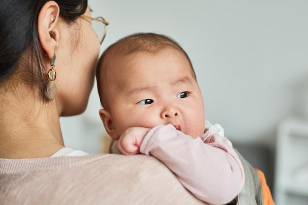 Vista posteriore della giovane madre che tiene la sua piccola figlia per mano e si prende cura di lei