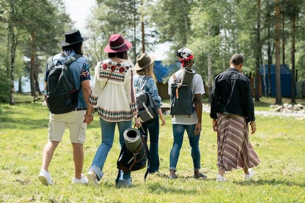 Vista posteriore di giovani amici multietnici con cartelle che camminano sul campeggio del festival mentre trovano posto per il campeggio