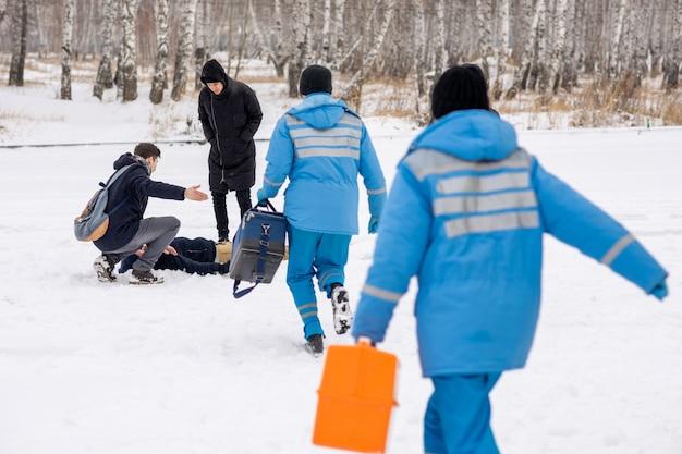 Vista posteriore di giovani paramedici in uniforme blu che si affrettano al malato che giace nella neve mentre due ragazzi si chinano su di lui