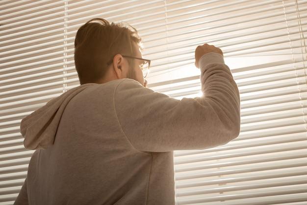 Vista posteriore del giovane uomo alla moda che dà una occhiata attraverso il foro nelle tende della finestra e guardando fuori in strada