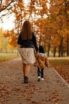 Vista posteriore su una giovane donna in un abito di moda e un bambino in abiti eleganti nel parco