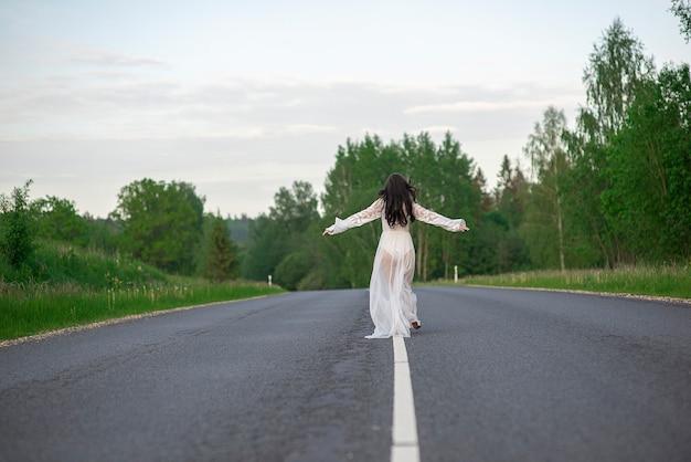 Vista posteriore di una giovane donna con un vestito bianco sexy che corre su una strada di campagna asfaltata vuota