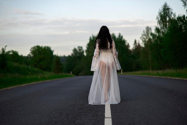 Vista posteriore di una giovane donna in un vestito bianco sexy in piedi su una linea di strada di campagna asfaltata vuota