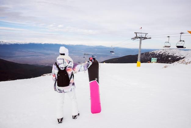 Vista posteriore della giovane donna con zaino e snowboard godendo in inverno nevoso sulla cima della montagna.