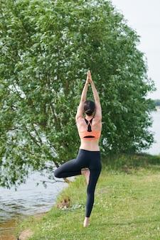 Vista posteriore della giovane donna con i capelli bun in piedi su una gamba e facendo esercizio di equilibrio all'aperto