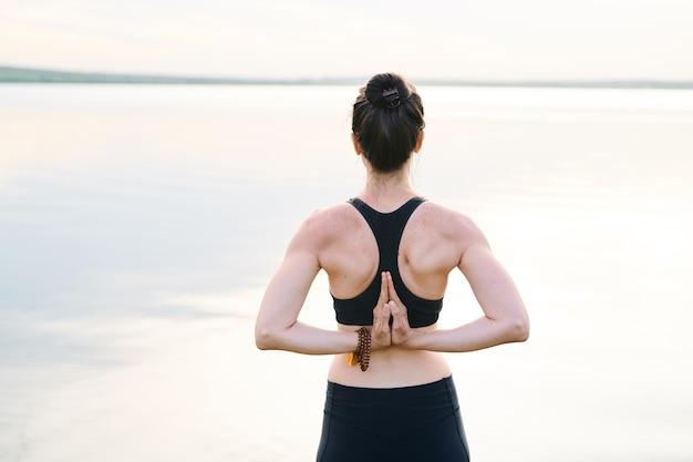Vista posteriore della giovane donna con la colonna vertebrale rafforzata in piedi contro il mare e unendo le mani dietro la schiena mentre si pratica yoga all'aria aperta