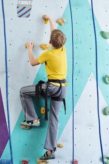 Vista posteriore del giovane ragazzo in maglietta gialla e pantaloni grigi salendo sulla parete lungo le funi mentre si afferra da piccole rocce