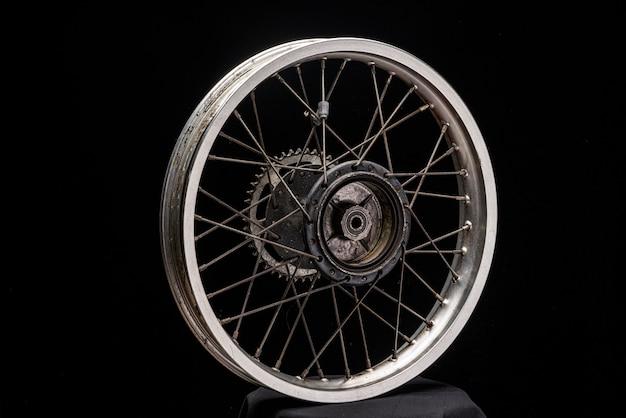 La ruota posteriore di una motocicletta senza pneumatico, vecchia usata. spazio nero del primo piano
