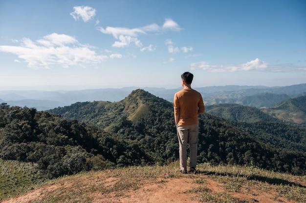 Parte posteriore del giovane uomo asiatico in piedi con guardando la vista sulle montagne in cima alla collina al parco nazionale