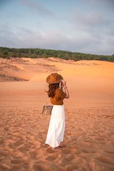 Parte posteriore della giovane donna asiatica che indossa il cappello in piedi sulla duna del deserto alla sera