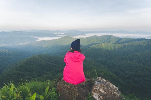 Parte posteriore della giovane donna seduta sulla roccia e vedere la vista sulla cima della montagna