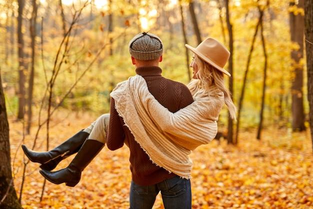 Rearview dell'uomo che tiene la ragazza nella sosta di autunno