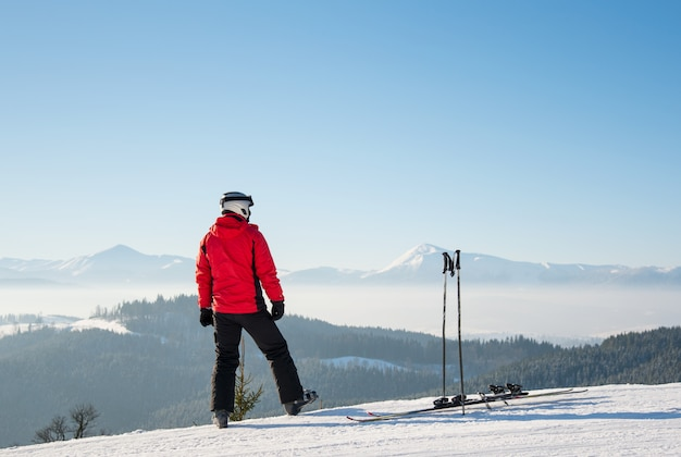 Colpo di retrovisore di uno sciatore che riposa dopo il giro in piedi sulla cima della pista da sci guardando intorno godendo la vista mozzafiato delle montagne innevate in una giornata di sole invernale