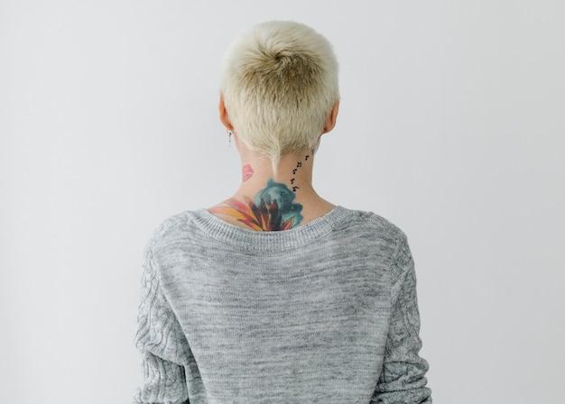 Retrovisore di una donna tatuata con un maglione grigio