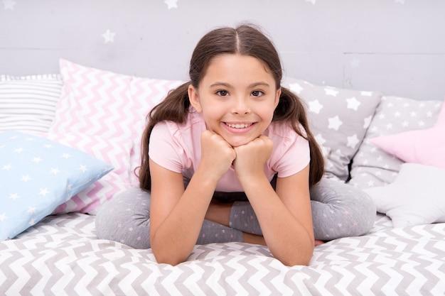 Motivo per sorridere. sorriso felice del bambino a letto. bambina con un sorriso carino. buona notte. sogni d'oro. odontoiatria. clinica dentale. salute dei denti. igiene dei denti. prenditi cura del tuo sorriso.