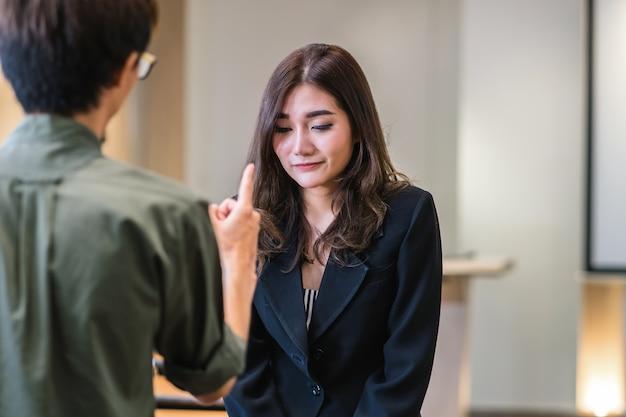 Vista di reaw del capo furioso che rimprovera giovane donna di affari asiatica
