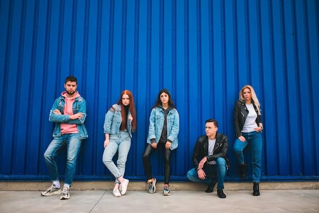 Ribelle. un gruppo di quattro giovani amici diversi in abito di jeans sembrano spensierati, giovani e felici camminando per le strade della città. moda di abiti urbani, libertà, amicizia, concetto di stile.