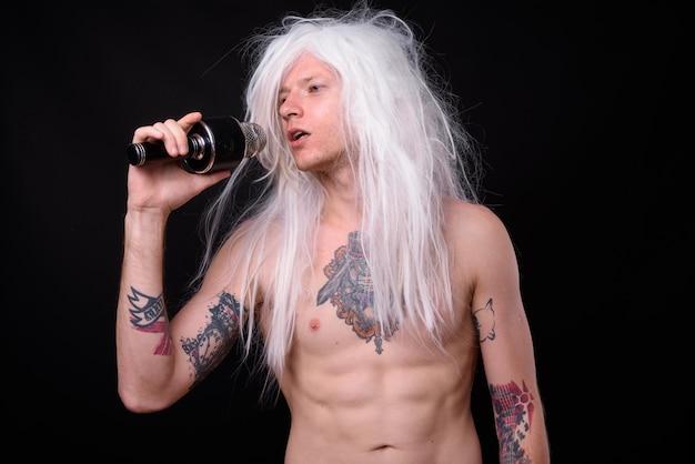 Uomo ribelle come punk rocker che indossa parrucca a torso nudo contro il nero