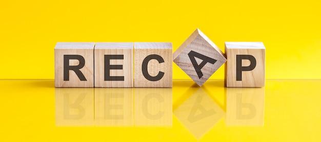 La parola recap è composta da blocchi di legno che giacciono sul tavolo giallo, concetto