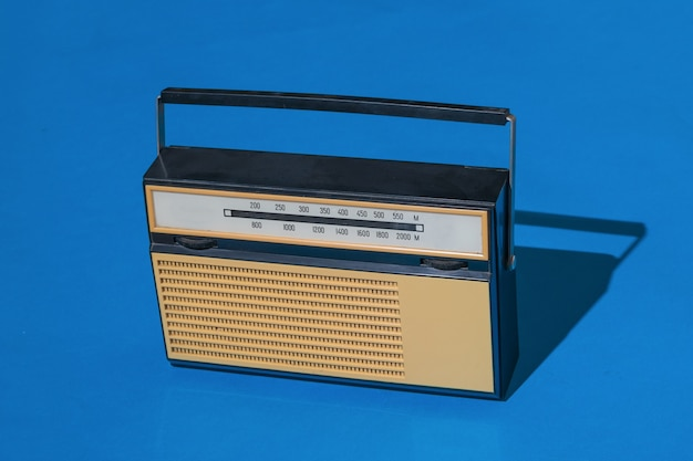 Un ricevitore per ascoltare le trasmissioni radio su sfondo blu. trasmissione radiofonica in diretta. tecnica vintage.