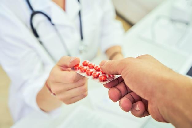 Alla reception e al medico. il medico ha prescritto farmaci e consegna il farmaco al paziente della clinica. concetto di farmacologia e assistenza sanitaria.