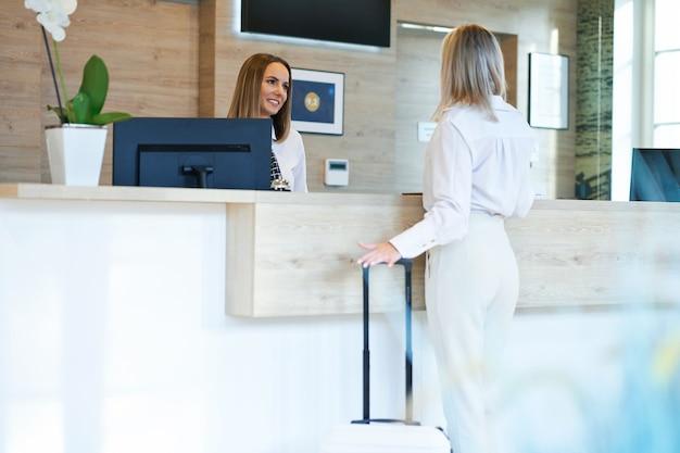 Receptionist e donna d'affari alla reception dell'hotel