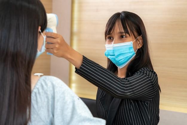 Receptionist e ospite che indossano la maschera facciale alla reception.