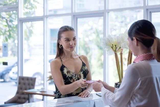 L'addetto alla reception consegna un passaporto a un turista alla reception e alla reception di un ostello