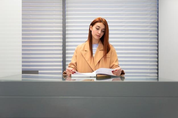 La donna della receptionist sfoglia il libro mastro