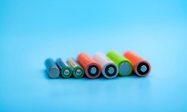 Batteria ricaricabile su sfondo blu. terminali positivo e negativo delle batterie agli ioni di litio ricaricabili. dimensioni aa e aaa della vecchia batteria agli ioni di litio. concetto di riciclaggio della batteria. energia verde.