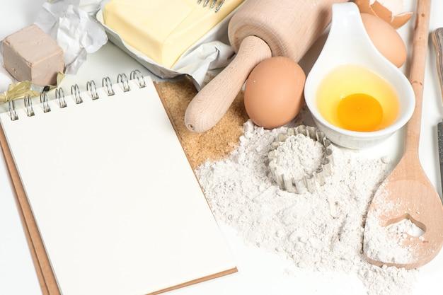 Ricettario e ingredienti per cuocere uova, farina, zucchero, burro, lievito