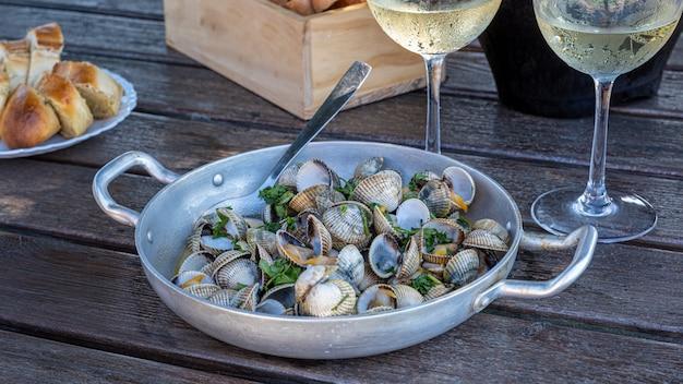 Ricetta per i cardi con aglio e prezzemolo in una casseruola di alluminio, accompagnati da una bevanda di champagne