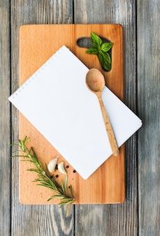 Concetto di ricetta. foglio di carta bianco su una tavola di legno con spezie