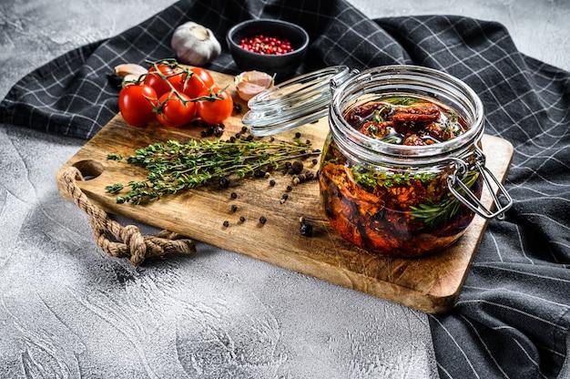 Ricetta per cucinare pomodori secchi in olio d'oliva con spezie ed erbe aromatiche. sfondo grigio. vista dall'alto. copia spazio