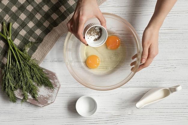 Ricetta per frittata di uova con aneto, mani femminili aggiungono pepe e sale