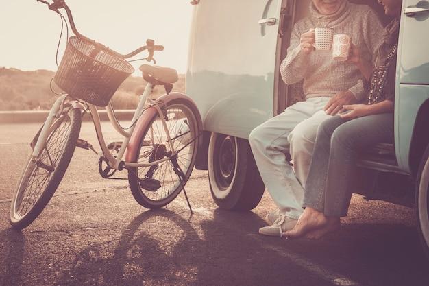 Non riconoscibile coppia di coppie caucasiche che si divertono e bevono caffè insieme seduti fuori dal vecchio furgone vintage con bici parcheggiata all'aperto -