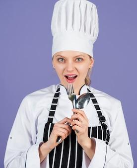 Consiglia una dieta equilibrata. pronto per mangiare. cuciniamo. felice cuoco usa cucchiaio e forchetta. preparazione della cena a casa. la cucina è il mio hobby. ritratto di donna chef. cucina premio. donna chef professionista.